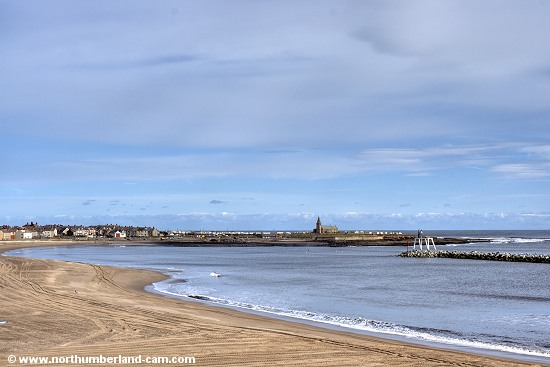 View across the bay and beach to the Church Point. The other beach at Newbiggin is beyond the point.